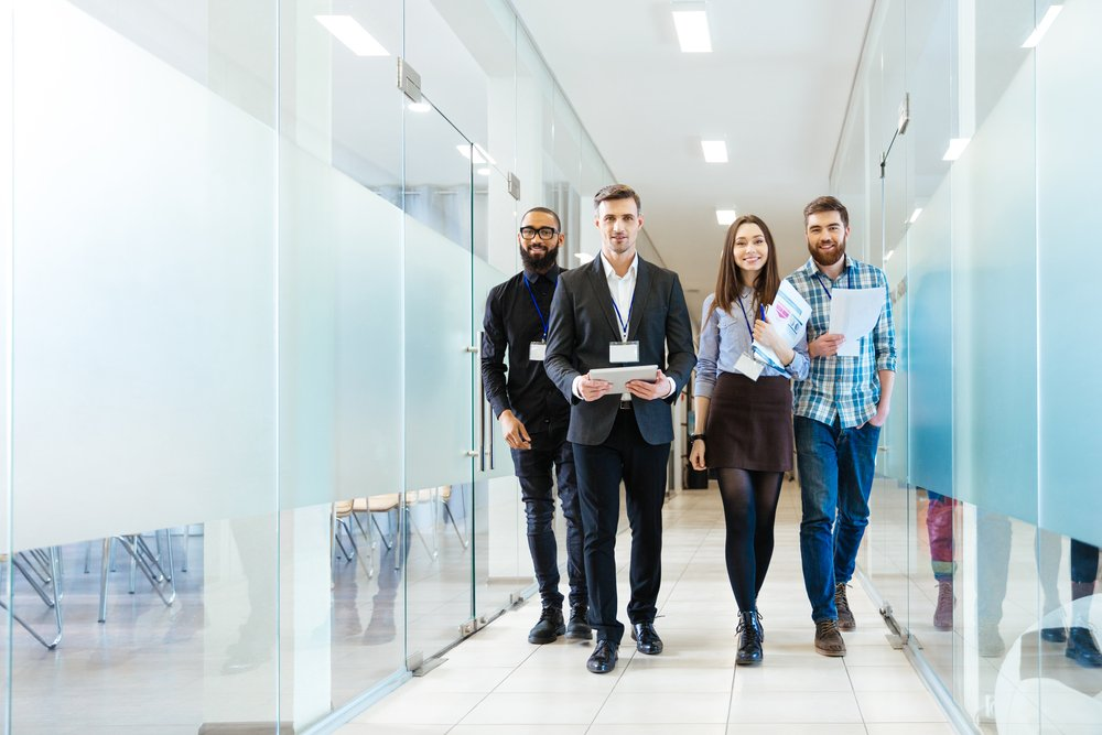Full-length-of-group-of-happy-young-business-people-walking-the-corridor-in-office-together