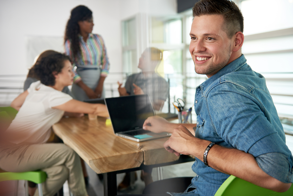Image-of-a-succesful-casual-business-man-using-laptop-during-meeting