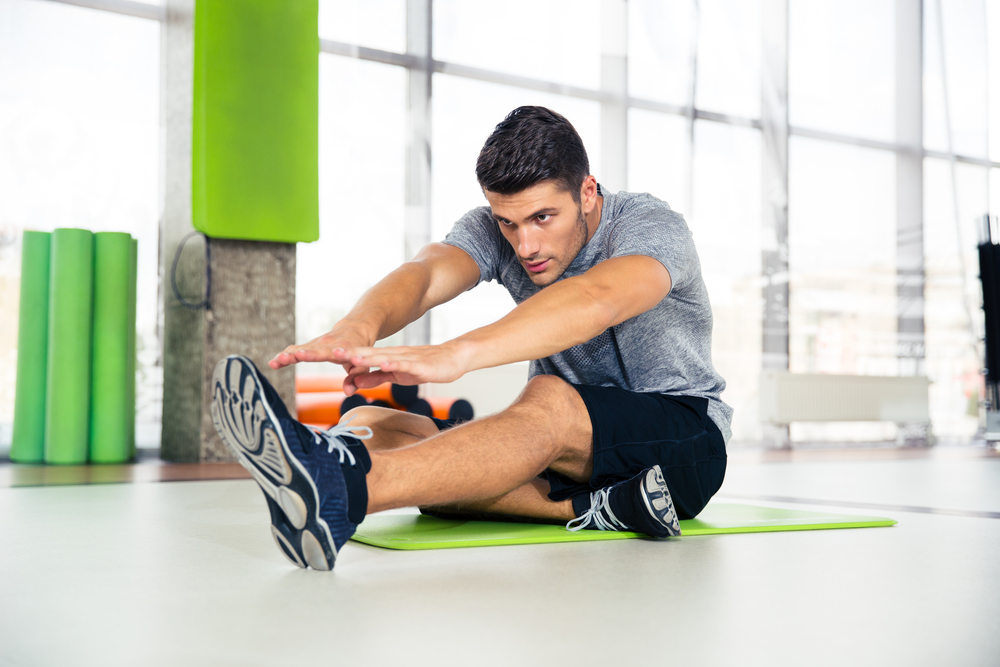 Portrait-of-a-fitness-man-doing-stretching-exercises-at-gym