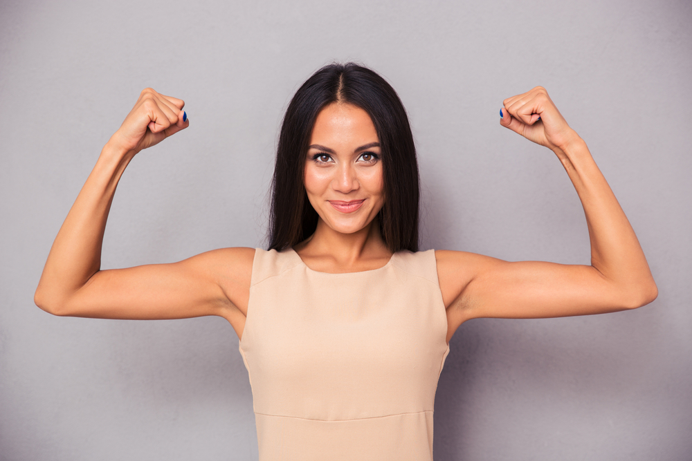 Portrait-of-a-happy-elegant-woman-showing-her-biceps-on-gray-background