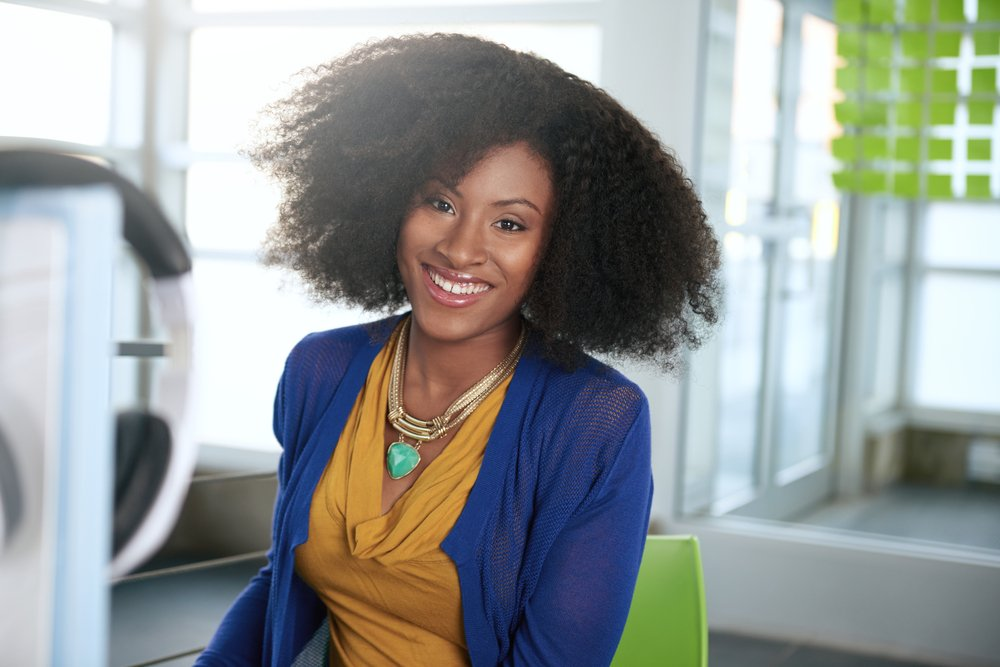 Portrait-of-a-smiling-woman-with-an-afro-at-the-computer-in-bright-glass-office