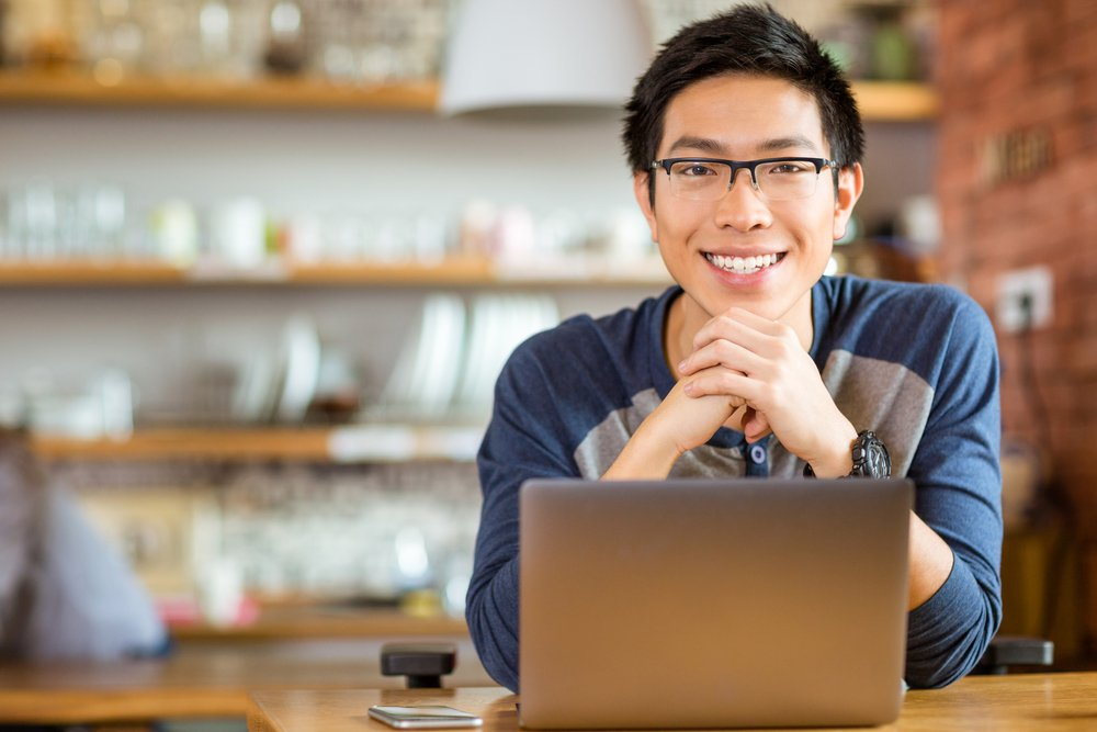 Portrait-of-positive-asian-male-in-glasses-with-laptop-in-cafe