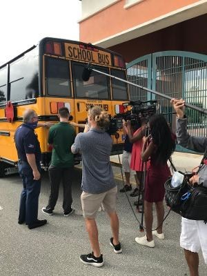 Rob Thomson, Realtor at Waterfront Properties with Jupiter High School Students as they place tag on the new bus.