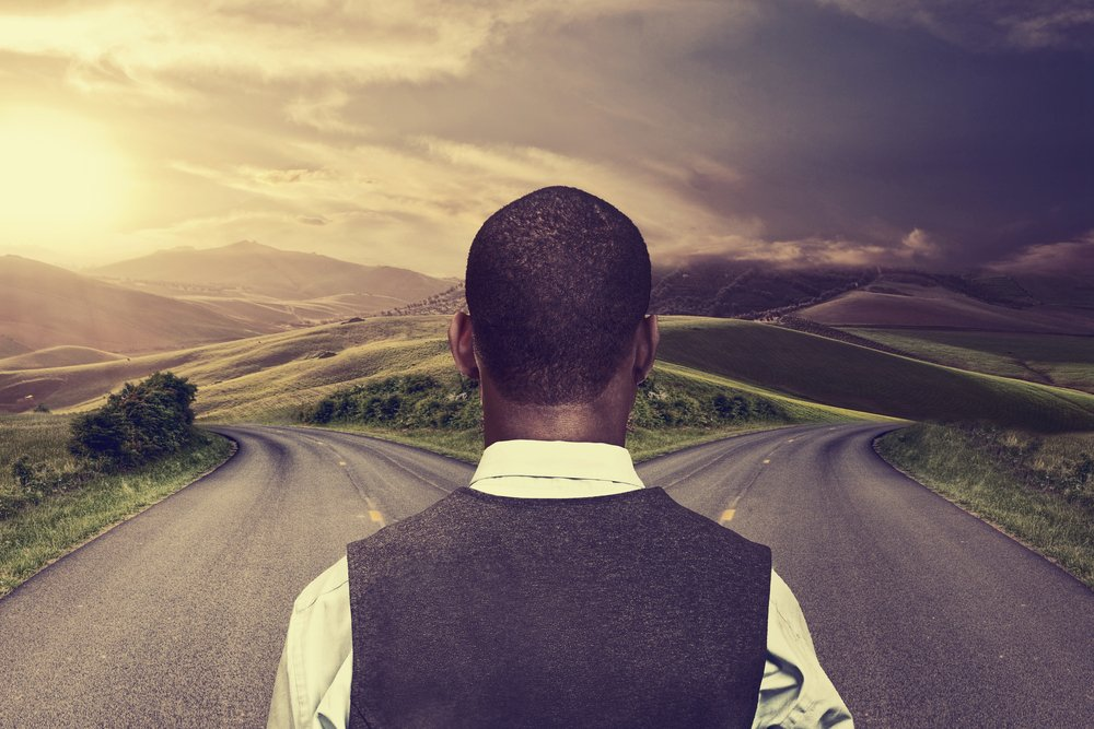 businessman-in-front-of-two-roads-hoping-for-best-taking-chance