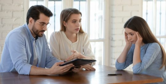 Female realtor stressed by difficult couple clients