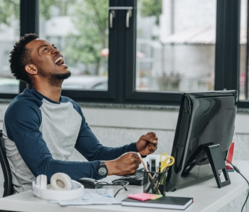 angry african american programmer gesturing while sitting at workplace in office