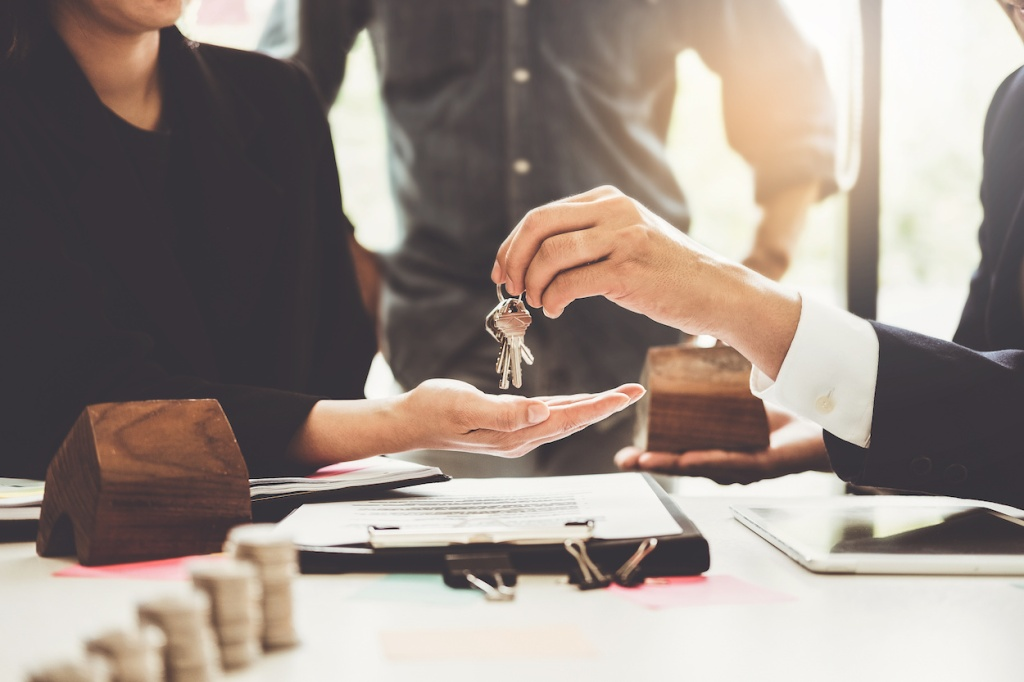 Agents are giving house keys of customer and holding dollar us bank at agency office. Agreement and real estate concept.