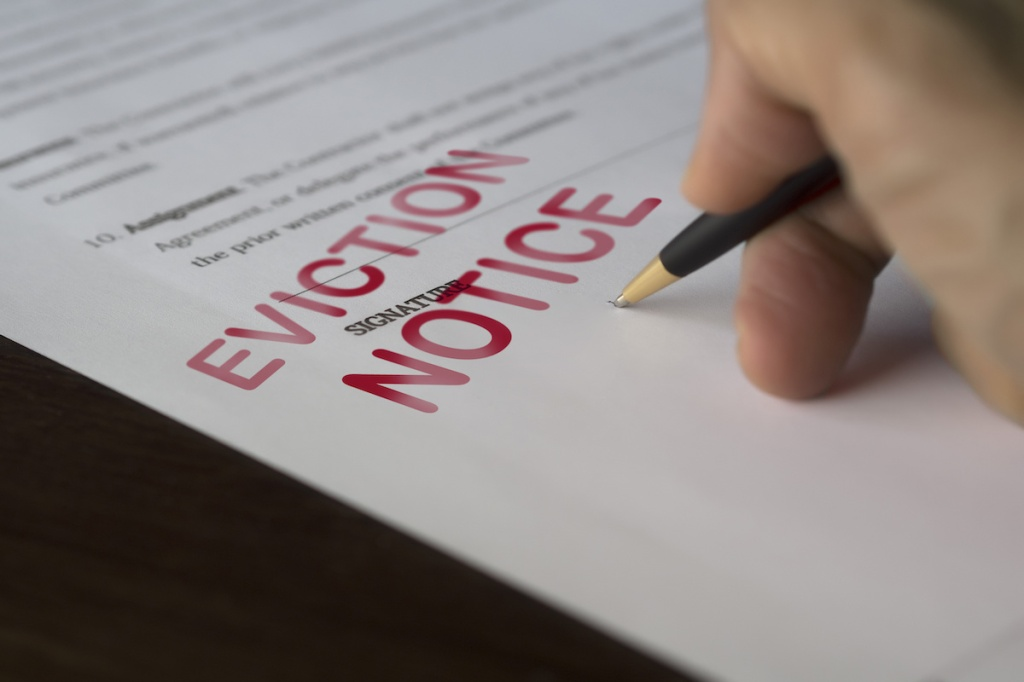 Man signing signing an eviction notice to a defaulting renter in due to missed rent in recession