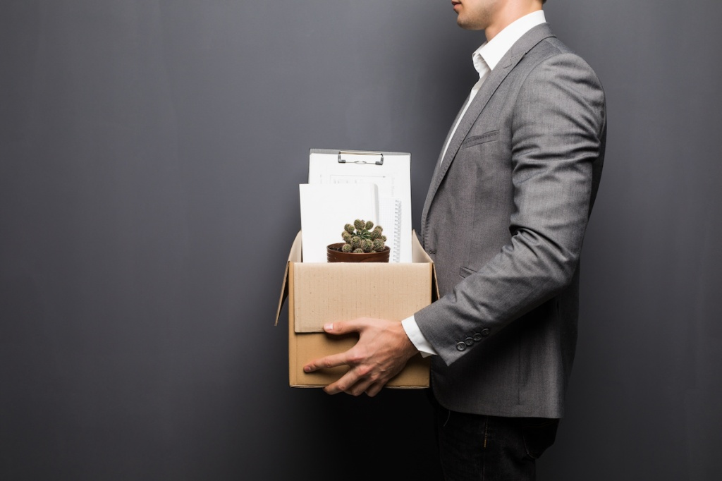 Close up of fired man employee hiding behind box with personal items on grey background